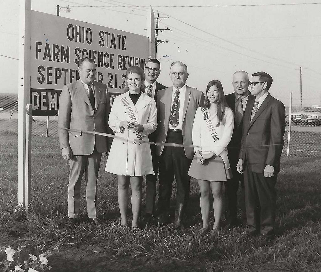 Ohio's Princess Soya Teresa Ludwig cut the ribbon for the opening of the 1971 Ohio Farm Science Review at Columbus. Approximately 70,000 farmers saw the over 100 demonstration plots of corn and soybeans during the 3-day session. A tour of next year's demonstrations will feature the annual American Soybean Association convention in Columbus in 1972. From left in the photo: M. David Urmston, deputy director, Ohio Department of Agriculture; Miss Ludwig; Dean Roy M. Kottman, Ohio State University College of Agriculture; Everett G. Royer, secretary-treasurer, Ohio Soybean Association; Connie Lett, Miss Ohio State Fair; Ed Sheid, member of the Ohio Expositions Commission; and Lawton McClintock, agriculture supervisor, Ohio State Fair.