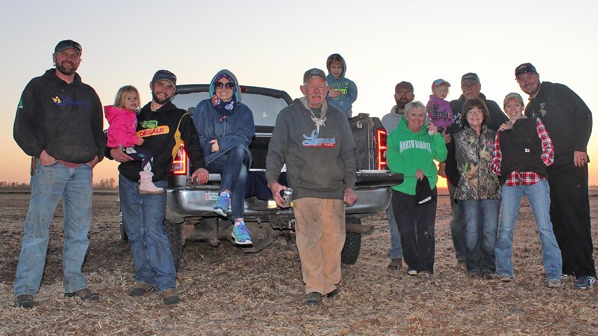 Photo of the entire farm family in a harvested soybean field.